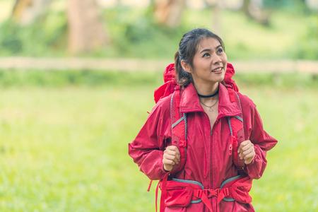 アジアの女性バックパッカーには赤いジャケット スタンドと夏の自然公園で楽しんで
