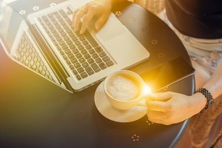 ラップトップでのカフェの共同作業しビジネス プランのメール チェックとコーヒーを飲みながら机に座って若い女性。食堂・売店、ヴィンテージ色