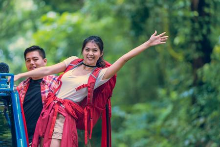 アジアの男性と女性のバックパッカーには、赤いジャケットが 4 wd 車の上に立って夏自然公園で楽しんで