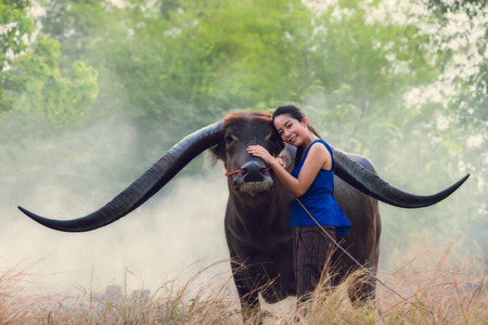 Portrait of Thai young woman farmer with buffalo