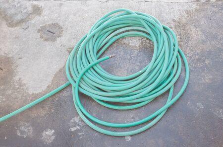 plastic conduit: Rubber tube for watering plants on wet floor Stock Photo