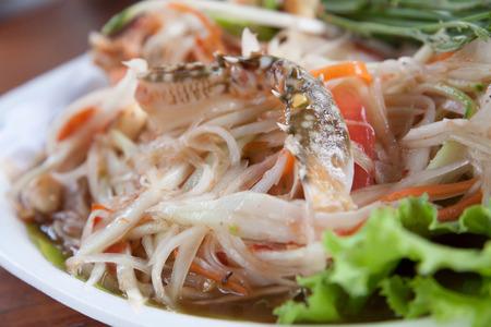 green papaya salad: Papaya Salad, Thai call Som tum the most famous thai salad combination of green papaya, green beans, carrots, garlic, fresh chili, cherry tomatoes and carrots with sliced fresh lettuce Stock Photo
