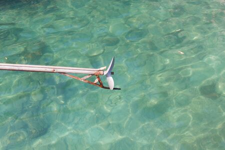 long tail: Long tail boat propeller in emerald sea.