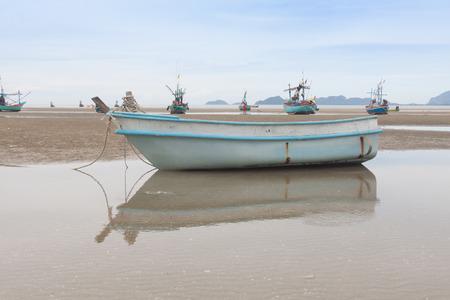 fiberglass: Reflection of fiberglass boat on  low tide beach .