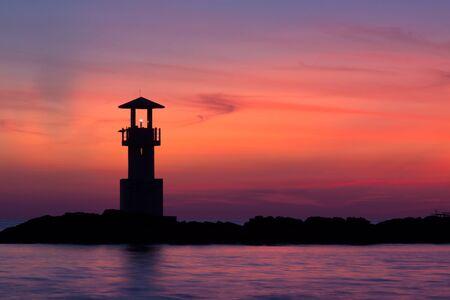 Seascape at sunset. Lighthouse on the coast Stock Photo