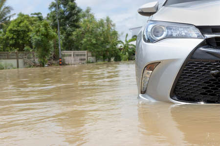 Cars driving on a flooded road, The broken car is parked in a flooded road. Reklamní fotografie