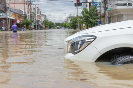 Cars driving on a flooded road, The broken car is parked in a flooded road.