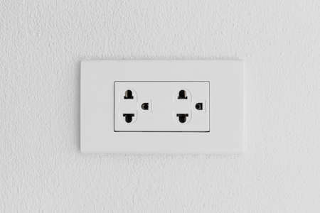 Electrical outlet on wall loft style,Power plug on white concrete wall, Energy socket.