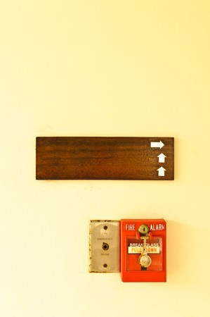 A fire alarm and wood board on the wall photo