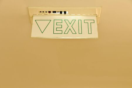 An exit sign mounted on  a ceiling photo