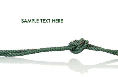 nudo: Green atado cuerda que est� hecho de nylon sobre fondo blanco con reflexi�n Foto de archivo