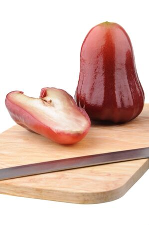 One and a half of red rose apple and a knife on chopping board isolated on white. Its scientific name is