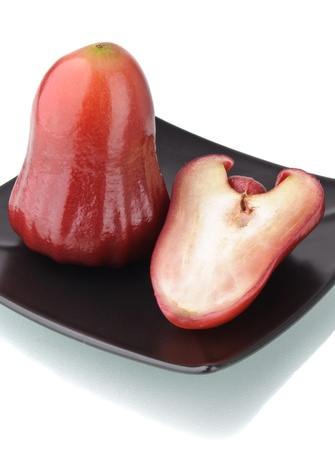One and a half of red rose apple on black plate isolated on white. Its scientific name is Syzygium samarangense photo