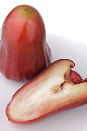 One and a half of red rose apple on white plate isolated on white. Its scientific name is