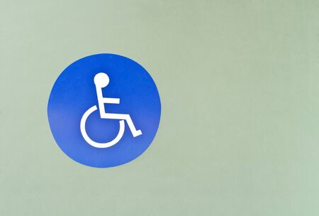 Blue wheel chair sign for  handicapped person in front of restrooms door photo