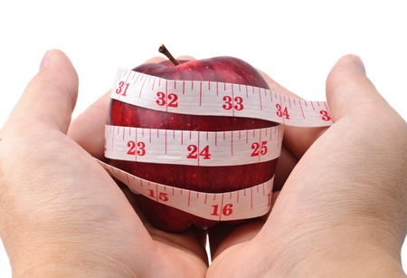hands holding a red apple with measuring tape isolated in white photo