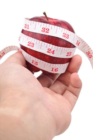 left hand holding a red apple with measuring tape isolated in white photo