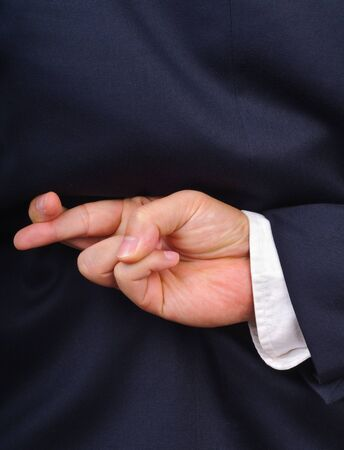 Close up of businessman with fingers crossed behind his back photo