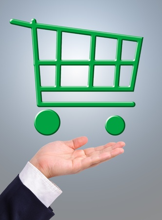Conceptual image, green shopping cart on business man's hand. Business man can help the earth by buying things with Stock Photo - 9676126