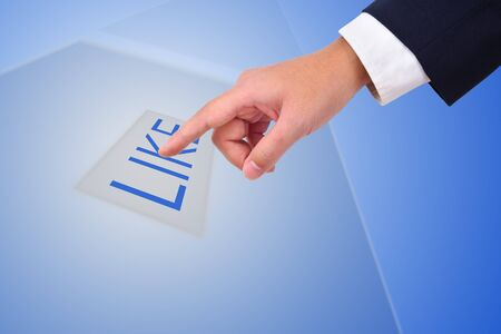 A hand of a business man is pressing like button with a blue background. photo