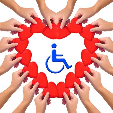 handicap: Immagine concettuale, un amore handicap persona. Mani con cuori isolata on white con icona blu sedia a rotelle al centro. Archivio Fotografico