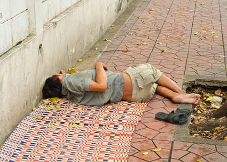 BANGKOK,THAILAND-SEPTEMBER 23: A homeless person takes a nap on a pavement on September 23,2011 in Bangkok, Thailand.