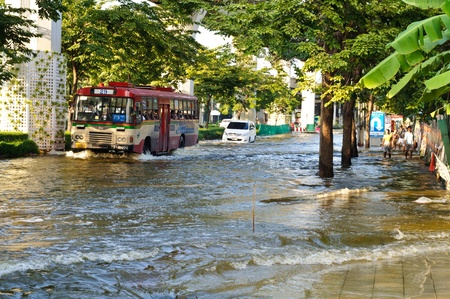 BANGKOK - NOVEMBER 10 : a bus, a car drive on a flooded road and people walk pass a flooded pavement near saphan kwai area on November 10, 2011 in Bangkok.