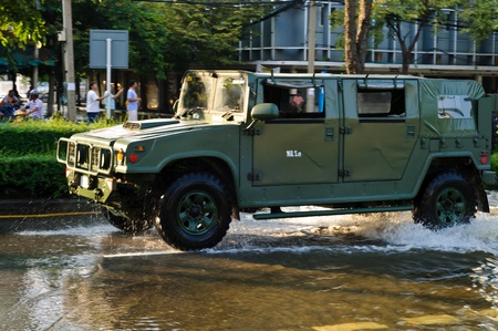 BANGKOK - NOVEMBER 10 : a military car drives on a flooded road near saphan kwai area on November 10, 2011 in Bangkok. Stock Photo - 11128393