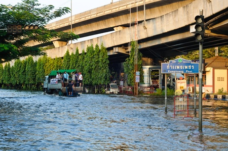 BANGKOK - NOVEMBER 10 : a truck with passengers drives on a flooded road during a severe flood situation at Kamphaeng Phet intersection on November 10, 2011 in Bangkok. Stock Photo - 11128602