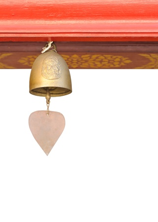 a small bell hanging under the temple roof on white background. photo