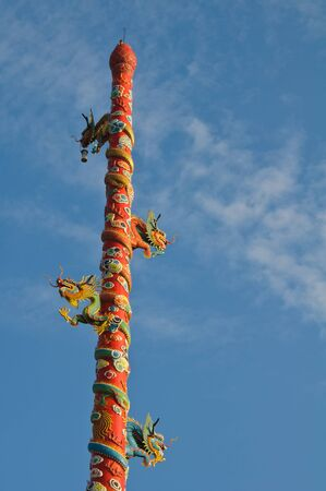 Chinese style dragon pole with blue sky in the evening, Thailand. photo