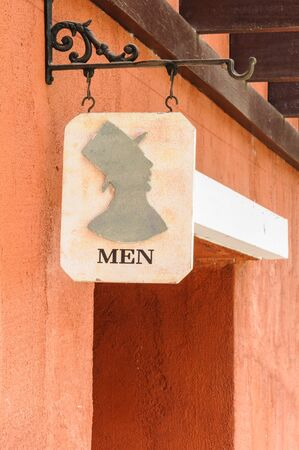 Men's public toilet sign in front of an entrance. photo