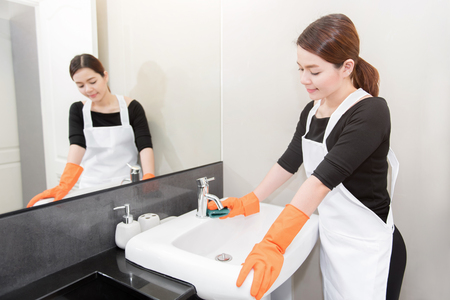 wall mirror: Asian young maid cleaning sink in bathroom, face reflected in the wall mirror, Cleaning service concept