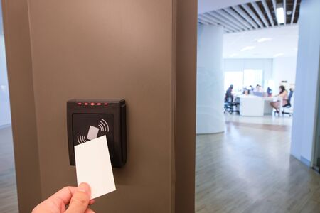 Men hand reaching to use RFID key card to access to office building area and workspace. In building security only for authorized person