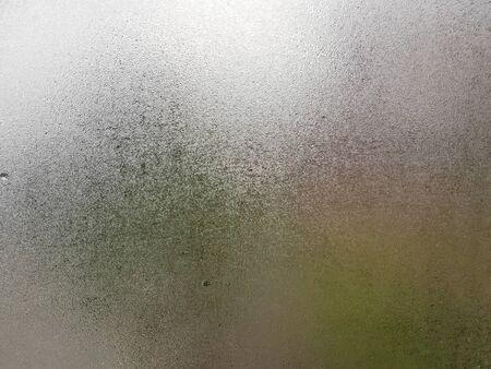 Transparentes Glas mit Nebel und Wassertropfen darauf während der Wintersaison mit kalter Handschrift darauf. Nahaufnahme des natürlichen Schönheitseffekts. Hintergrund- und Tapetenkonzept.
