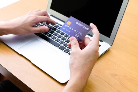 Men hand holding credit card and type payment information on keyboard for order online shopping. Internet technology and Digital market place E-Commerce lifestyle concept, Purchase transaction.