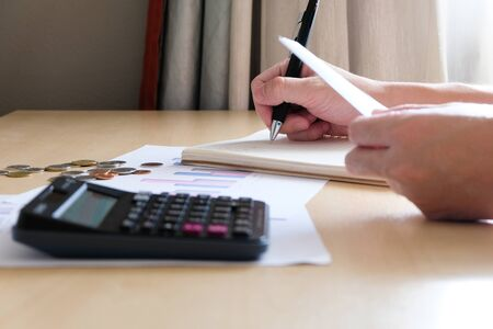 Selective focus of Men using calculator, holding invoice and check his salary for plan personal expense budget. Individual balance sheet for saving and payment control. Financial and economy concept.