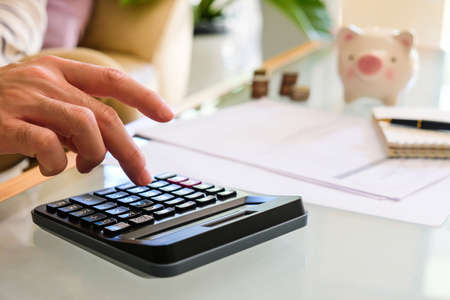 Selective focus of Asian men hand while calculate for personal saving with document and piggy bank at the background.