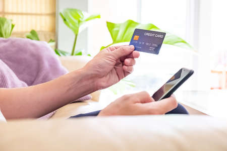 Selective focus at men hand holding credit card while type payment information into smartphone. Online purchase transaction during social distance period.