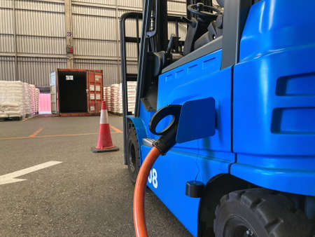 Electrical forklift vehicle park and plug in for charging battery inside of logistic warehouse. Alternative energy source for car and machine in industrial business segment. Automotive technology. Imagens
