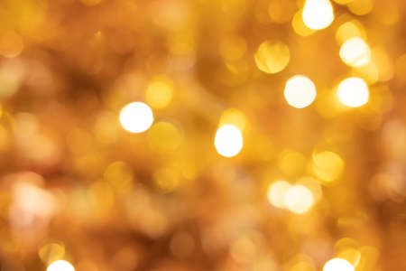 Blurred defocus shot of yellow or golden decorating light bokeh. That people decorate during Christmas celebration period. Ideal for wallpaper and background.