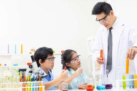 Young boy and girl doing science experiment with colorful liquid chemical inside glass tube and beaker. With teacher who teach and give instruction in classroom. Science and education concept. Stockfoto