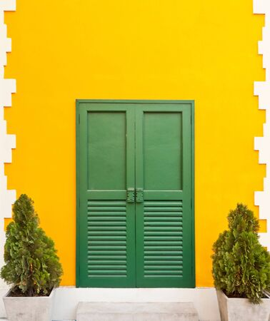 Beautiful and funny yellow house with green door Stock Photo