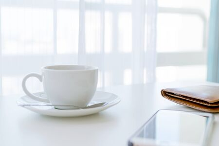 Coffee time in the morning, coffee cup with smartphone and wallets.