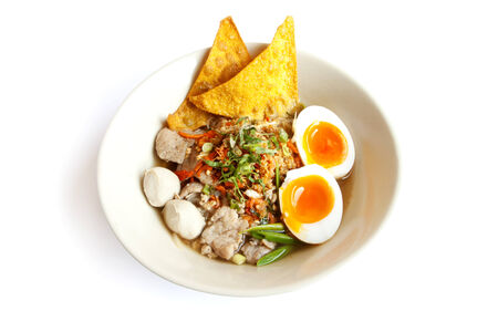 Thai noodle soup with pork ball and egg.  photo