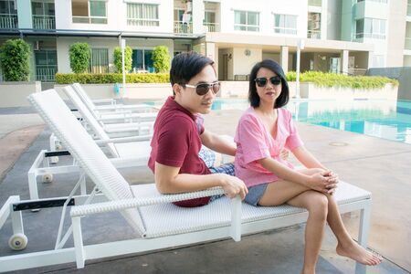 asian man and women siting on white sofa, beatiful woman ware black glasses, couple happy and smile at swimming pool.