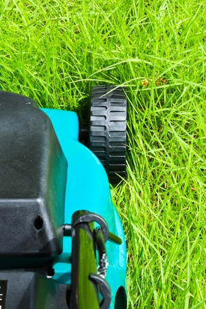 Lawn mover is going to be operated over long grass with backside view photo