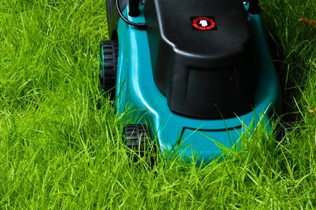 Lawn mover is going to be operated over long grass with front side horizontal view photo