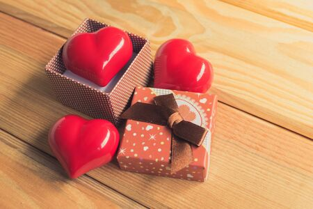 hearty: Gift of love. hearty gift. A gift box with a red heart inside. On the wooden floor Stock Photo