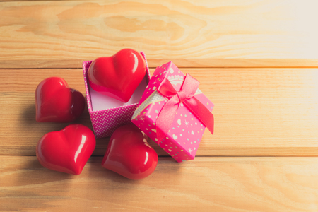 Gift of love. hearty gift. A gift box with a red heart inside. On the wooden floor Stock Photo